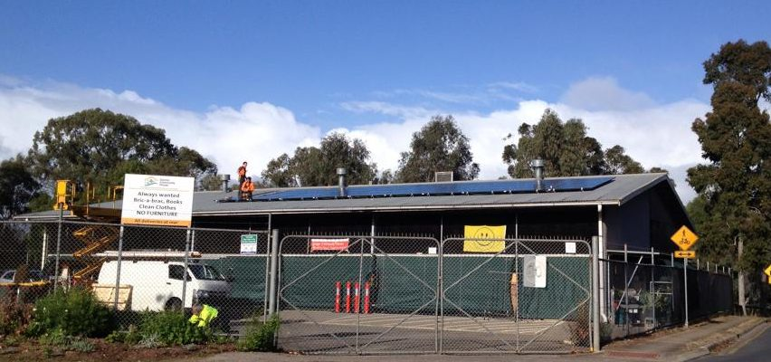 Workers installing solar panels on Gawler Community House roof